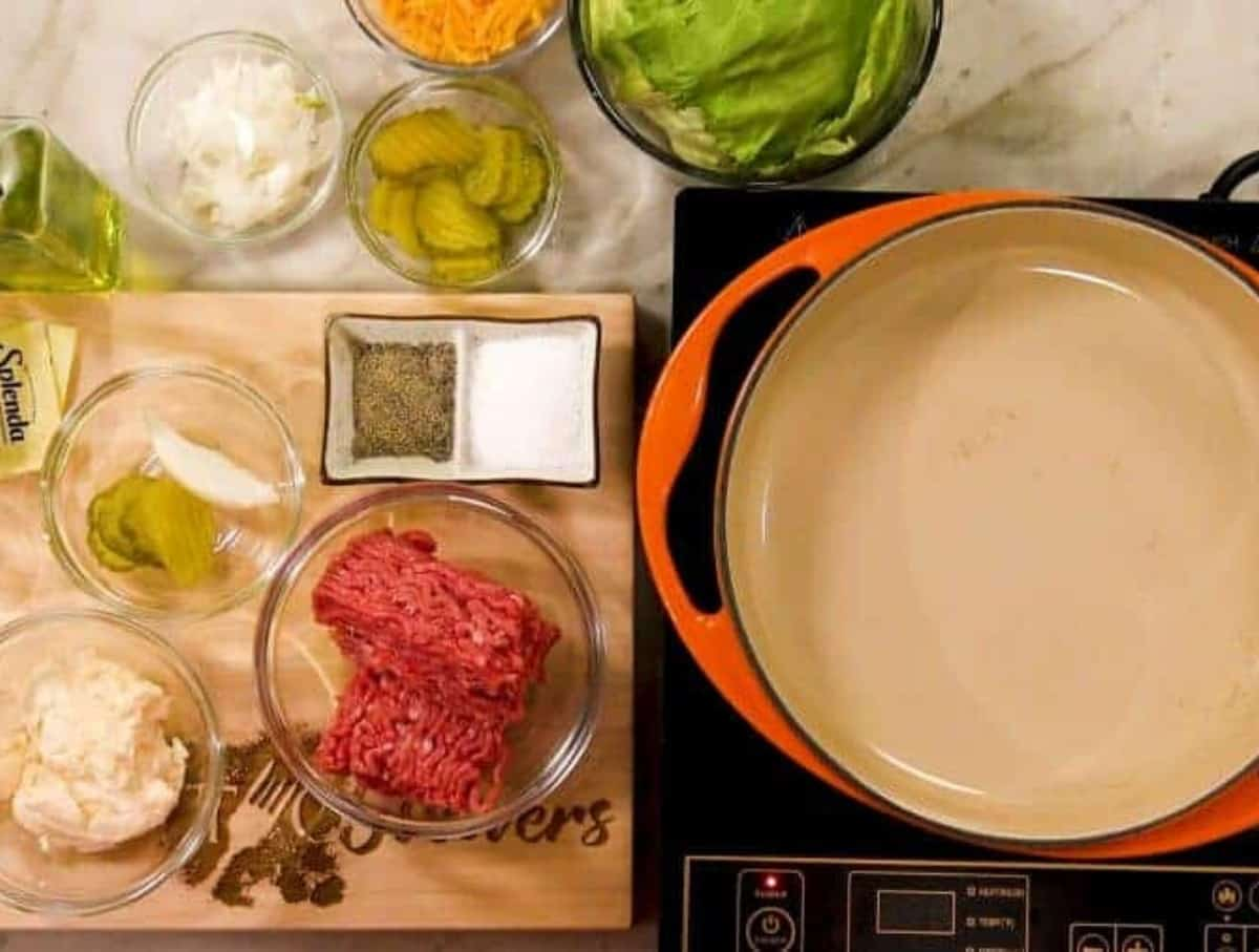 An orange ceramic pan on an induction burner with ground beef, mayo, pickles and onions, and salt in pepper in separate bowls to the side.