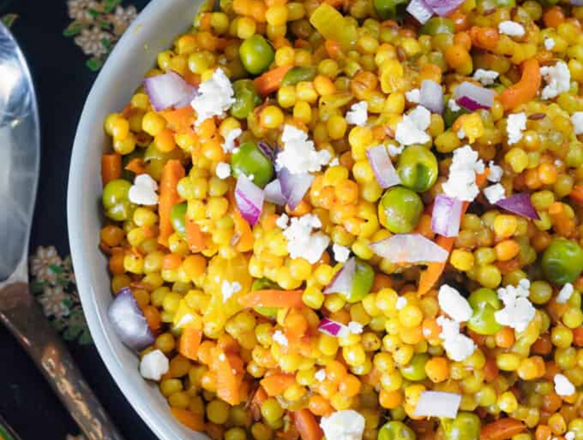 Beautifully vibrant colors in an Israeli Couscous Salad served in a white bowl.