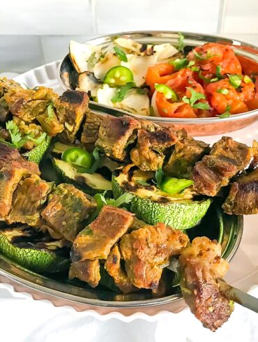 Grilled beef kebabs served on top of vegetables