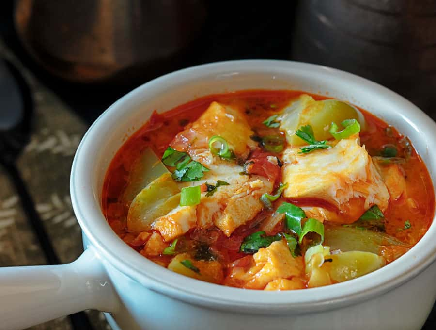 Brazilian Moqueca Fish Stew served in a white bowl with a handle.