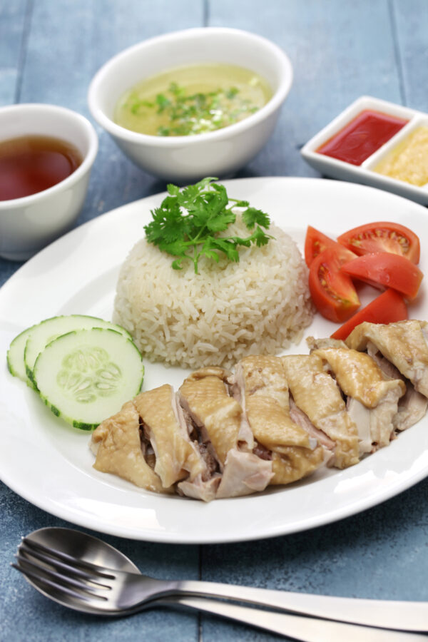 Hainanese Chicken and Rice served on a white plate with omatoes and cucumber.