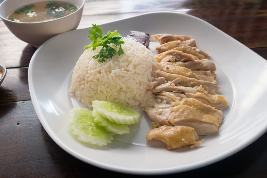 Hainanese Chicken Rice dish served on a white plate with a bowl of soup in the background.