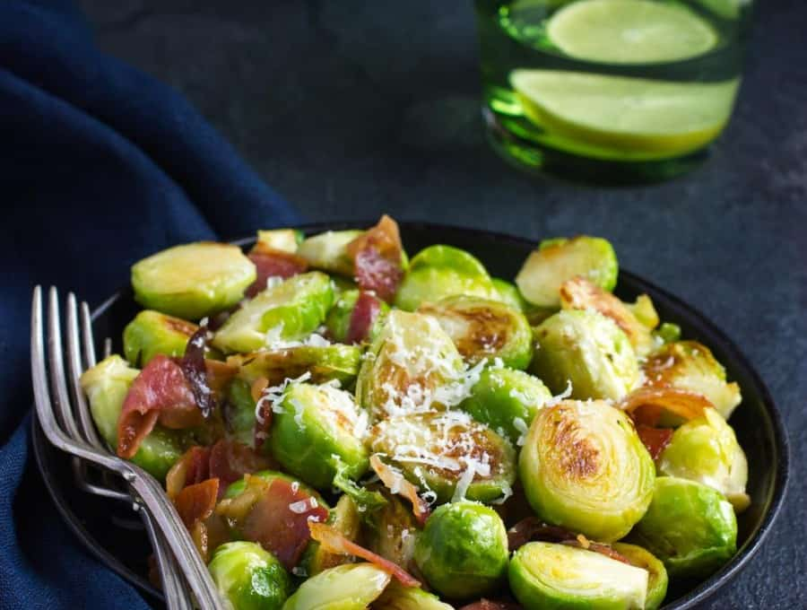 Image of roasted brussel sprouts with bacon in a black bowl with two forks laying to the side.