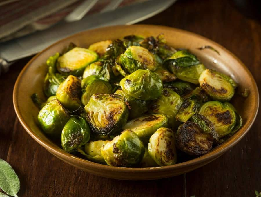 Overhead image of roasted brussel sprouts with bacon in a ceramic bowl.