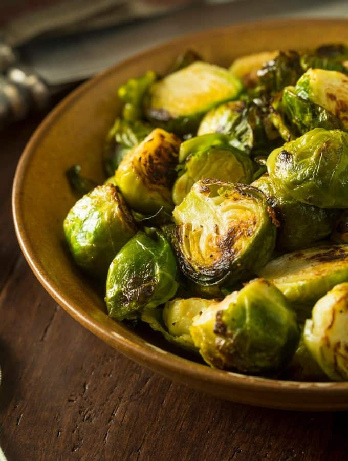 Vertical image of roasted brussel sprouts with bacon served in a ceramic bowl.