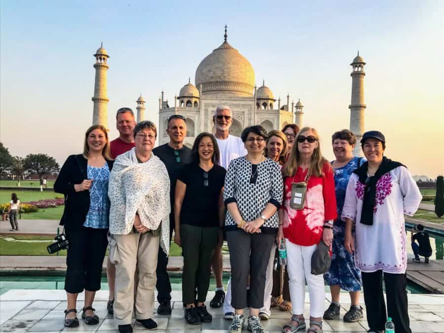 A group of people posing for a photo in front of the Taj Mahal