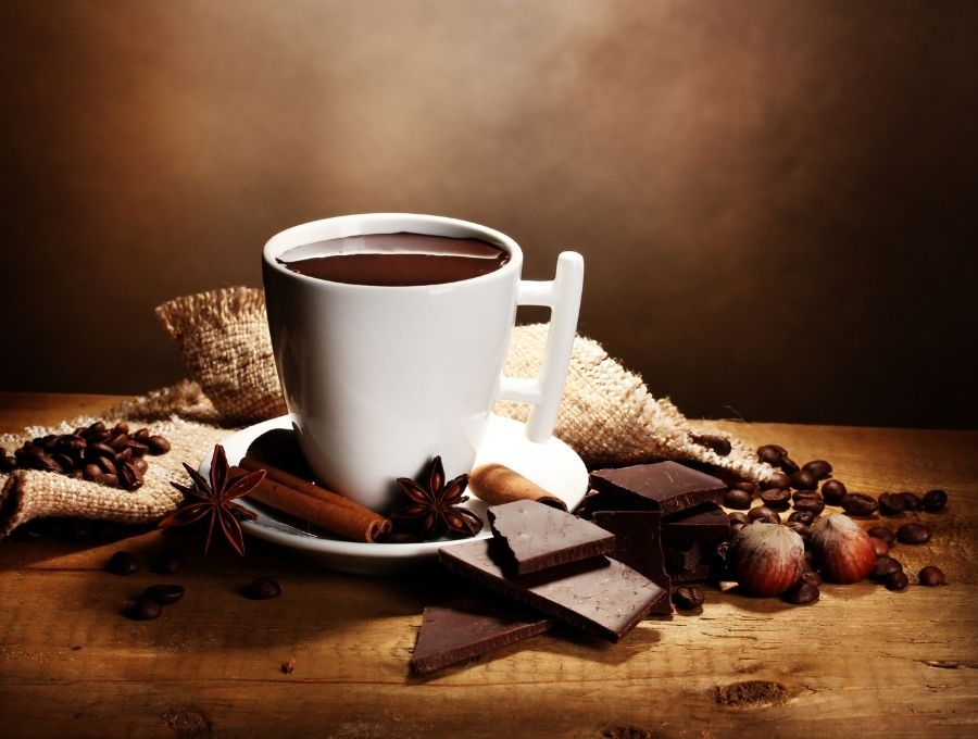 A white mug of keto hot chocolate surrounded by chocolate and cinnamon sticks
